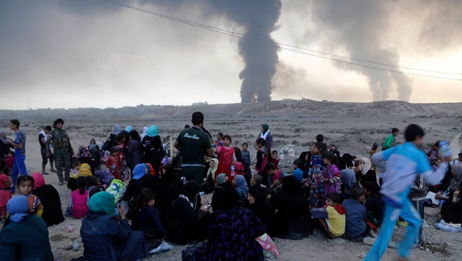 Smoke rises as people flee their homes during clashes between Iraqi security forces and members of the Islamic State fleeing Mosul, Iraq, on  Oct. 18, 2016.