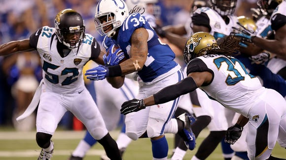 Indianapolis Colts running back Trent Richardson (34) ran by Jacksonville Jaguars strong safety Johnathan Cyprien (37), right, in the first half.