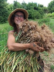 Stephanie Davis holds an armful of garlic.