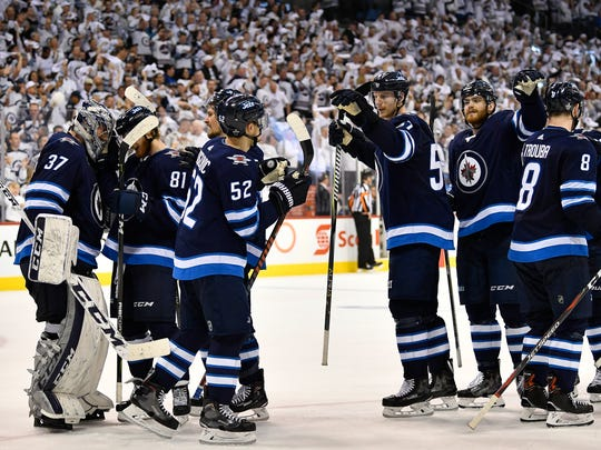 Winnipeg Jets congratulate goaltender Connor Hellebuyck (37) after their 7 to 4 victory over the Nashville Predators in Game 3 of the second-round NHL Stanley Cup playoff series at Bell MTS Place in Winnipeg, Manitoba, Canada, Tuesday, May 1, 2018.