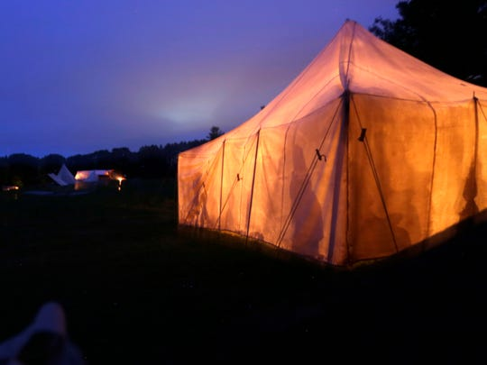 Shadows reflect onto a period-correct tent at night