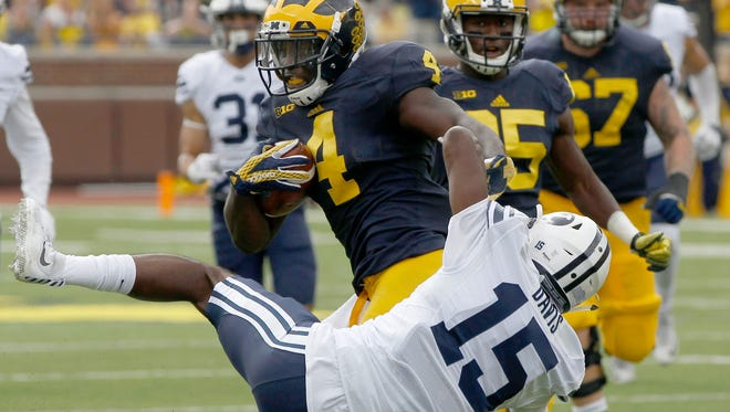 Michigan running back De'Veon Smith broke this tackle by Brigham Young's Michael Davis on his way to a 60-yard touchdown run in the second quarter Saturday.