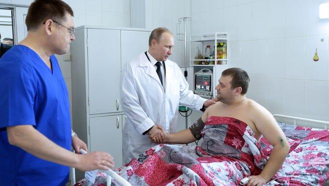 Russian President Vladimir Putin visits a terror attack victim Wednesday in Volgograd.