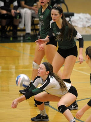 Novi's libero Claire Pinkerton (white jersey) serve receives in front of teammate Paulina Iacobelli.