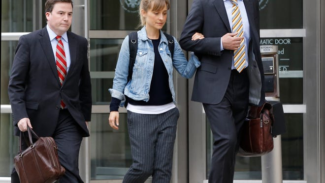 Allison Mack, center, leaves federal court, Tuesday, April 24, 2018, in the Brooklyn borough of New York. Federal prosecutors say the television actress best known for playing a young Superman's close friend has been charged with sex trafficking for helping recruit women to be slaves of a man who sold himself as a self-improvement guru.