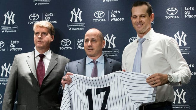 New York Yankees owner Hal Steinbrenner, left, general manager Brian Cashman, center, and Aaron Boone, pose for photographers during a news conference introducing  Boone as the baseball team's new manager, Wednesday, Dec. 6, 2017, at Yankee stadium in New York.