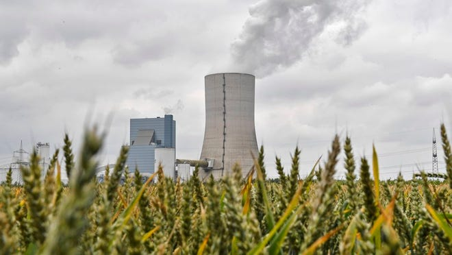 The controversial most modern Uniper Datteln 4 coal-powered plant steams behind a corn field one month after the operational start in Datteln, Germany, Friday, July 3, 2020. The state governors Dietmar Woidke of Brandenburg, Michael Kretschmer of Saxony, Reiner Haseloff of Saxony-Anhalt and Armin Laschet of North Rhine-Westphalia meet in Berlin for the adoption by the Bundestag and Bundesrat of the laws on coal phase-out and structural strengthening in the affected federal states.