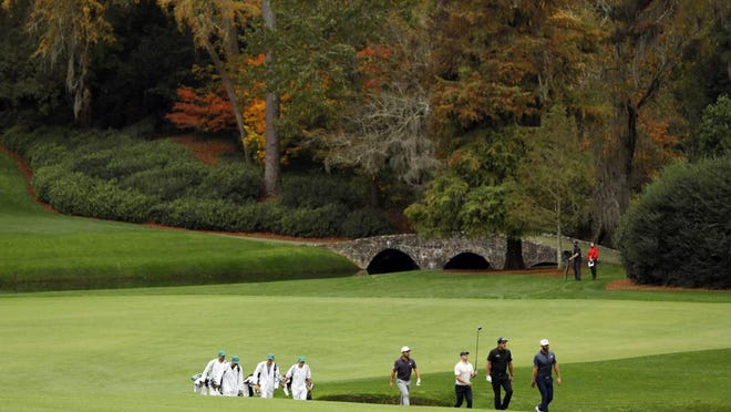 The foliage near the No. 13 fairway is colored in fall hues for the rescheduled 2020 Masters Tournament. Above, Xander Schauffele, Rory McIlroy, Phil Mickelson and Dustin Johnson walk along the No. 13 fairway during Tuesday's practice round at Augusta National Golf Club.
