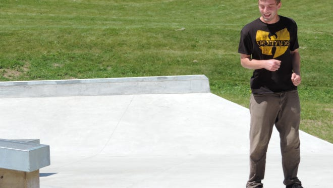 Wes Payne, 26 smiles as he lands a trick on the new skate park at Kiwanis Park in Sheboygan on June 28.