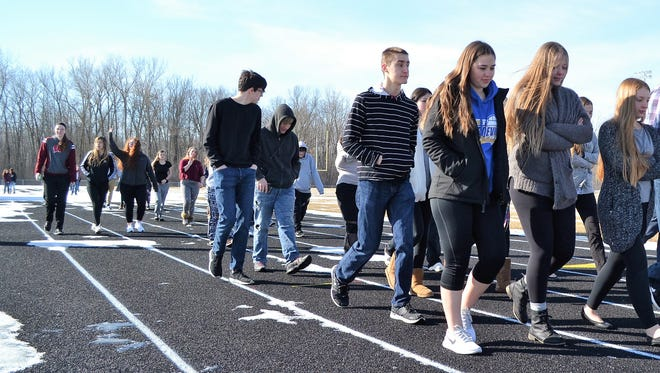 Oconto High School students walk on the track during the national student walkout to protest violence in schools and stand with the victims of the school shootings in in Florida last month.