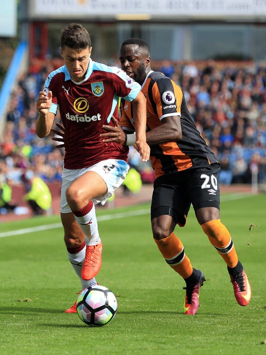 Burnley's Matt Lowton, left, and Hull City's Adama Diomande battle for the ball during the English Premier League soccer match at Turf Moor, Burnley, England, Saturday Sept. 10, 2016. (Clint Hughes/PA via AP)