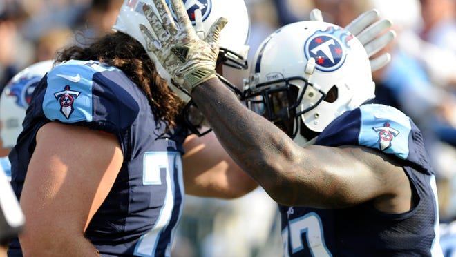 Titans offensive tackle Dennis Kelly (71) congratulates Titans tight end Delanie Walker (82) on his touchdown Sunday.