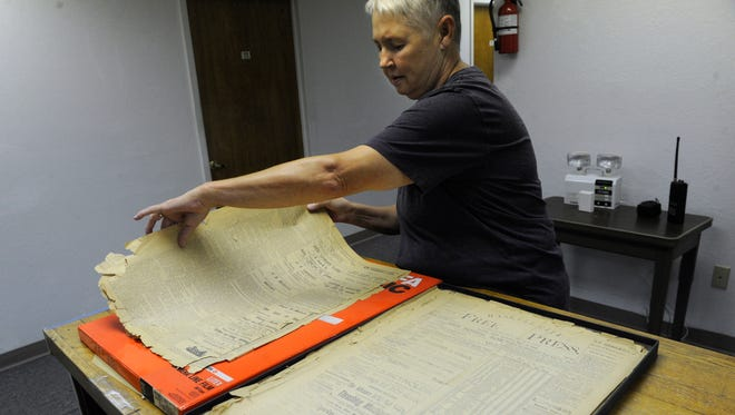 Lisa Shaw delicately turns over an April 3, 1886 copy of the Haskell Free Press Wednesday August 30, 2017. After 131 years, the newspaper published its last edition Thursday.