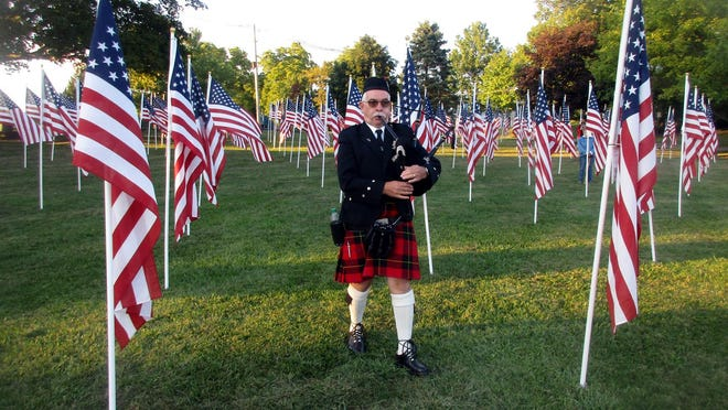 Bagpiper Dan Skinner plays as he walks through the field of American flags Sept. 11 during the 9/11 Remembrance Ceremony at Reilly-Mumford Memorial Park in Sherrill.