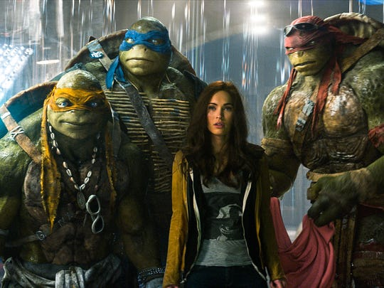 Michelangelo, Leonardo, Megan Fox as April O'Neil, Raphael, and Donatello in TEENAGE MUTANT NINJA TURTLES, from Paramount Pictures and Nickelodeon Movies.