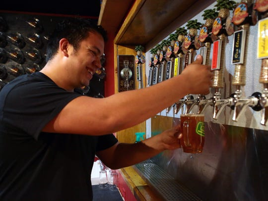 Taproom manager Michael Renteria pours a customer's