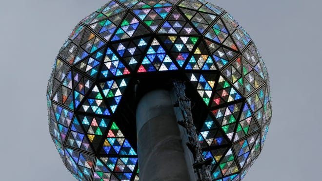 Workers light the Waterford crystal ball during a test for the New Year's Eve celebration atop One Times Square in New York, Tuesday, Dec. 30, 2014. The ball, which is 12 feet in diameter and weighs 11,875 pounds, is decorated with 2,688 Waterford crystals and illuminated by 32,256 LED lights.