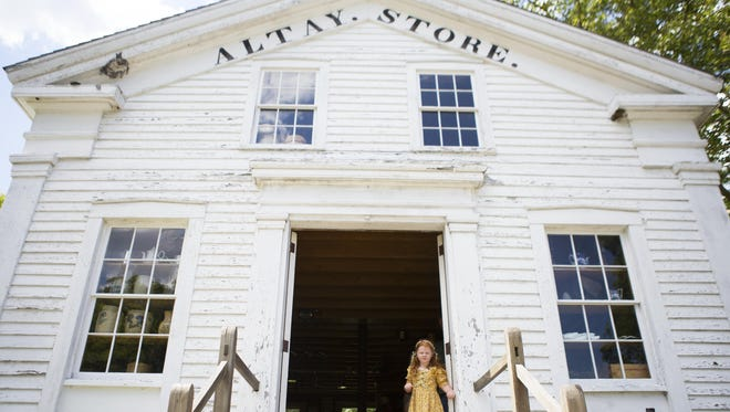 Elise Olsen, 5, of Albion stands in the doorway of the Altay Store earlier this month at the Genesee Country Village & Museum in Mumford.