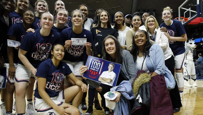 The UConn women's team and alumni celebrate the Huskies' 100th win in a row.