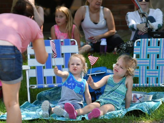 Patrick Clay, 2, and his sister, Melody Clay, 5, right, pose for their mom, Michele Verbeke of St. Clair Shores while she takes a photo at the 66th Annual St. Clair Shores Memorial Day Parade in St. Clair Shores, Mich. on May 27, 2018.