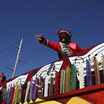 A member of the Krewe of Boogaloo throws beads to the crowd during an Alexandria Mardi Gras Parade in 2009.