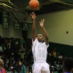 Bossier's Quatavious Capers rises up to shoot over three Woodlawn defenders in a 52-47 win.