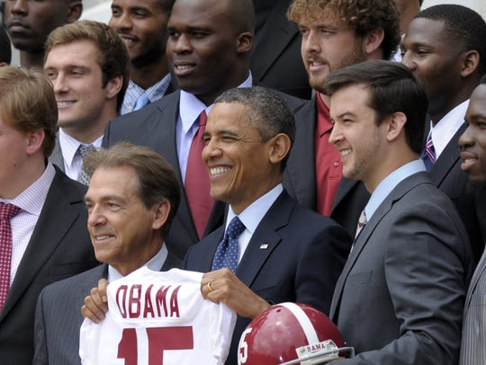 President Barack Obama holds up the Alabama Crimson