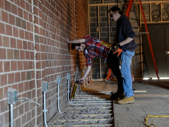 Nick Neuina junior at Lebanon High School and Andrew Kujovsky a senior at Cedar Crest High School work on the floor as students from the Lebanon County Career and Technology Center work on remodeling a building at the Lebanon County Fire School on Thursday, March 10, 2016.