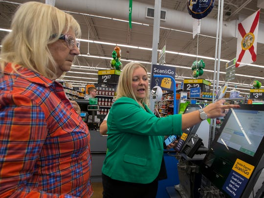 Adrienne Pope, store manager for Walmart Neighborhood Market in Cape Coral, assists part-time Cape Coral resident Mardi James, use the new bar code scanner check-out process, Tuesday, March, 13.  Walmart's new Scan & Go allows customers to scan items as they shop in-store and skip the checkout line.