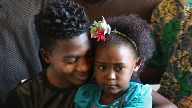 Withrow High School soccer player Daniel Sumuni tries to get his sister Happy, who had just awakened from a nap, to smile in his family's small Millvale apartment.