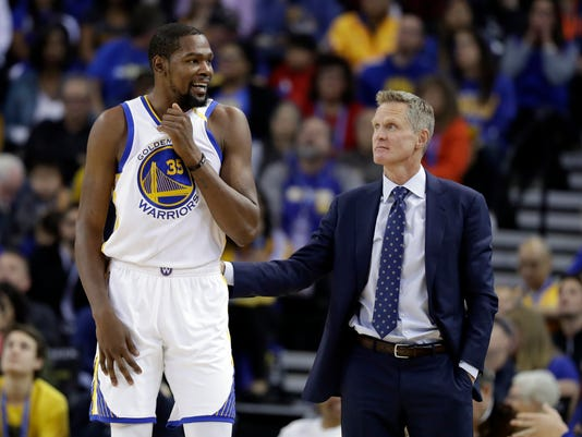 FILE - In this Nov. 23, 2016, file photo, Golden State Warriors' Kevin Durant, left, talks with coach Steve Kerr during the team's NBA basketball game against the Los Angeles Lakers in Oakland, Calif. Durant won't play later Saturday, April 22, in Game 3 against the Portland Trail Blazers because of a strained left calf. The Warriors will also be without Kerr because of an illness. Mike Brown will serve as acting coach. (AP Photo/Marcio Jose Sanchez, File)