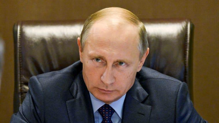 Russian President Vladimir Putin listens during a meeting