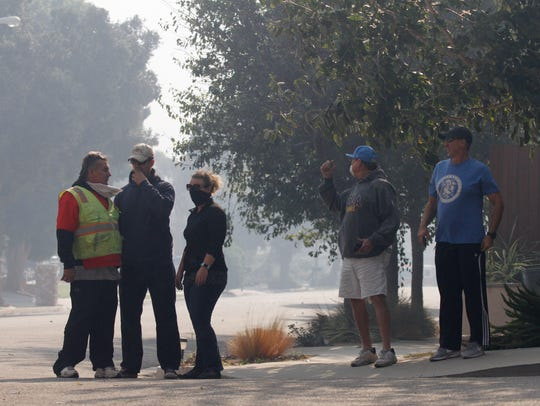 Local residents watch as firefighters battle the Thomas