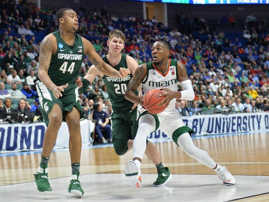 Mar 17, 2017; Tulsa, OK, USA; Miami Hurricanes guard Ja'Quan Newton (0) drives to the basket as Michigan State Spartans forward Nick Ward (44) and guard Matt McQuaid (20) guard during the second half in the first round of the 2017 NCAA Tournament at BOK Center. Mandatory Credit: Brett Rojo-USA TODAY Sports