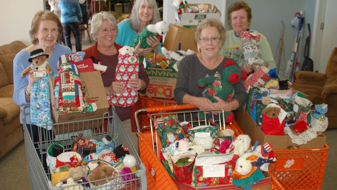 Members of The Material Girls (first row, from left) Mary Bouras, Kathleen Sinclair and JoAnn Moore and (second row) Kay Lisiecki and Carol Beasley are shown with the cartloads of handmade items they delivered Thursday to the Christmas Wish Center. Betsy Wooley was not available for the photo.