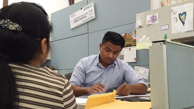 Adan Pacheco, 22, helps a client at Catholic Charities in Lakewood. Pacheco is an undocumented immigrant who received deferred action under President Obama's executive action on immigration that allows him to obtain a work permit and avoid deportation. 