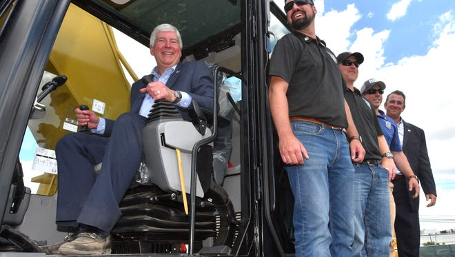 Michigan Gov. Rick Snyder poses with member of the Operating Engineers 324 on an excavator.