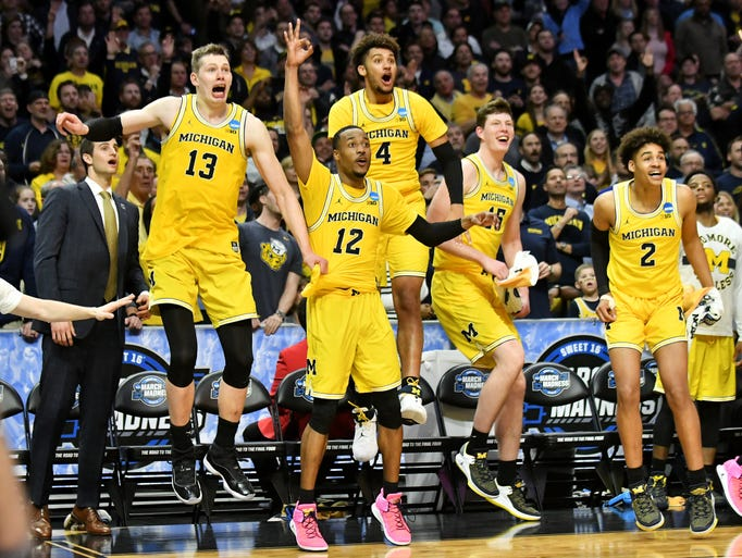 Players on the Michgan bench react after Michigan forward