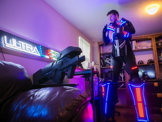 Spencer Bahnsen at his Pike Creek home getting into the Ultra LED Man suit.