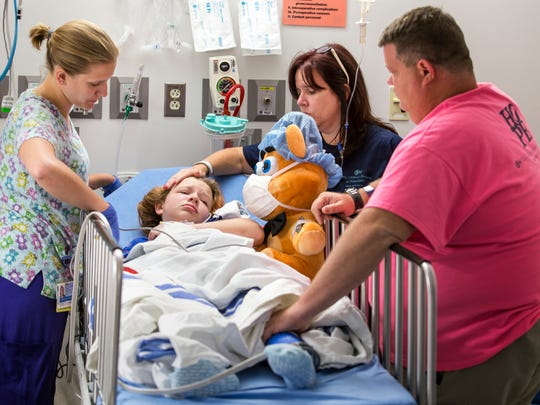 Todd and Maria Ruckle comfort their daughter Emily as she recovers shortly after her 12th surgery on her right arm.