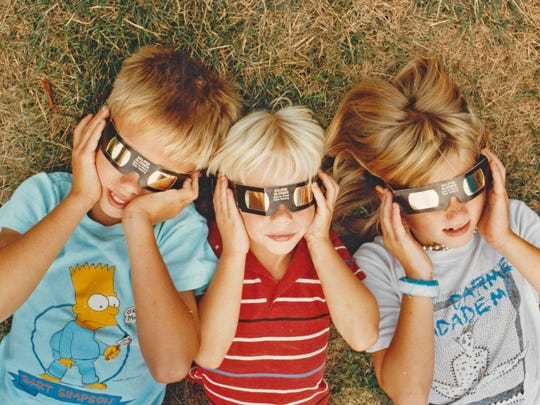Jennifer, John and Jason Rigsby of Carmel lie on the grass outside Holcomb Observatory and attempt to watch the sun's eclipse in 1991.