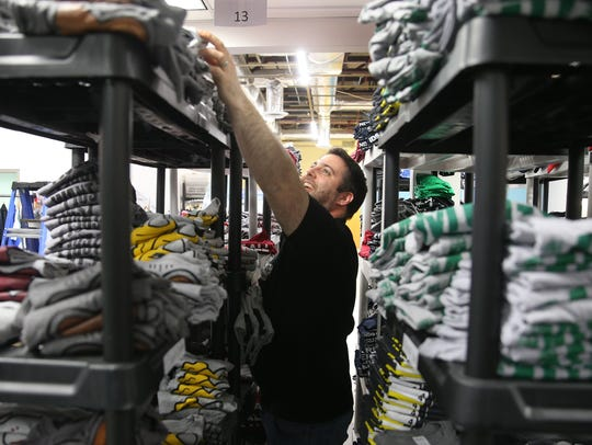 Pete Borelli gathers shirts on shelving at Crazy Dog