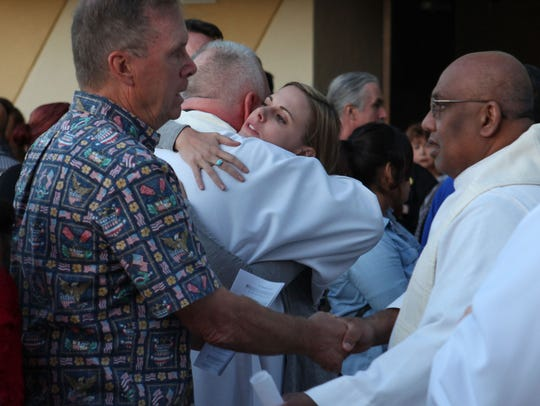 People gather and hug after an interfaith prayer service