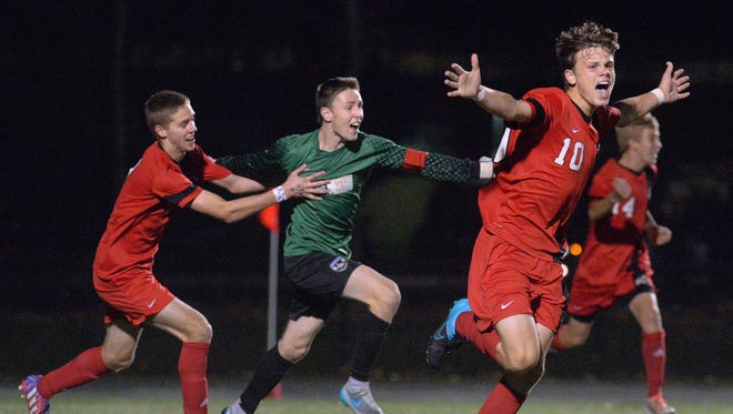 Hilton's Simon Garno, right, and teammates Brian Wilkin, center, and Michael Provost celebrate after the final whistle of the Section V Class AA Championship played at Spencerport High School on Tuesday, November 3, 2015. Hilton won the title 1-0 over Fairport.