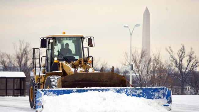 A plow clears a Pentagon parking lot after snowstorm.