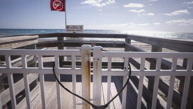 A combination lock has been placed on gate at Midtown Beach to prohibit people from entering after the Town of Palm Beach decided to close its beaches on March 17.