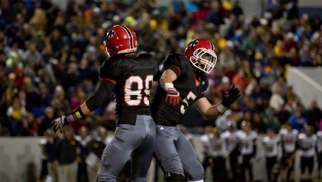 Port Huron junior Clay Carter, left, celebrates with sophomore Cameron Enright after scoring a touchdown during the Crosstown Showdown Friday, October 23, 2015 at Memorial Stadium in Port Huron.