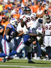 Denver tight end Virgil Green  is upended by Bills Tre'Davious White after a reception.
