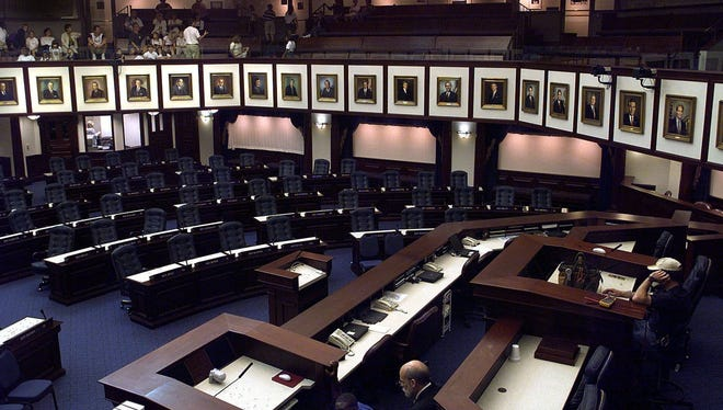 Workers (lower right) make last-minute preparations in the Florida House of Representatives chamber on March 3, 2000, in Tallahassee. Portraits of past House speakers, all men, are mounted on the wall. Vero Beach's Erin Grall hopes to become the first woman to serve as the House speaker.