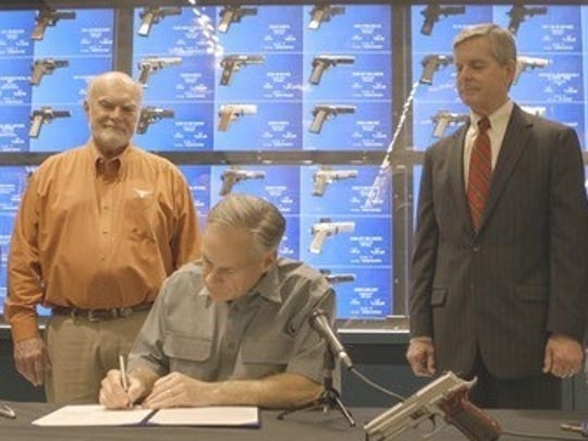 Texas Gov. Greg Abbott (center) signs a bill lowering fees for handgun licenses with the measure's authors, state Sen. Robert Nichols, left, and Rep. Phil King on May 26, 2017.